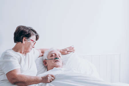 Photo pour Elderly lady comforting her ill husband lying in a white hospital bed - image libre de droit