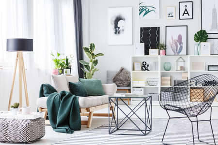 Photo pour Black chair near a table, pouf and settee with green cushions in bright living room interior with wooden lamp and posters on the wall - image libre de droit