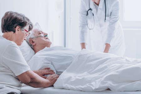 Foto de Doctor pronouncing death of an elderly patient in a presence of his spouse - Imagen libre de derechos