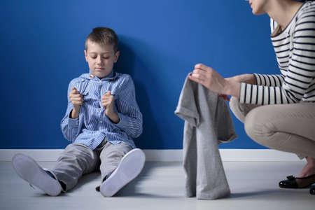 Foto de Mother taking care of kid with Heller syndrome sitting on the floor against blue wall - Imagen libre de derechos