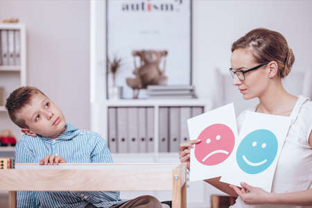 Foto de Counselor with posters of red and blue icons teaching autistic kid of good and bad behaviors - Imagen libre de derechos