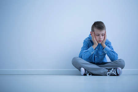 Foto de Depressed boy with Asperger syndrome sitting alone against a wall with copy space - Imagen libre de derechos