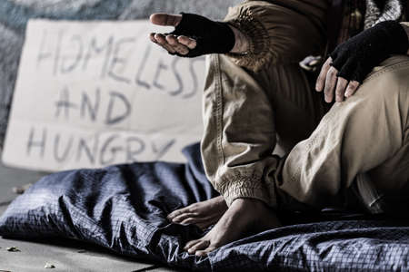 Photo pour Close-up of dirty and barefoot street person sitting on a blanket and begging - image libre de droit