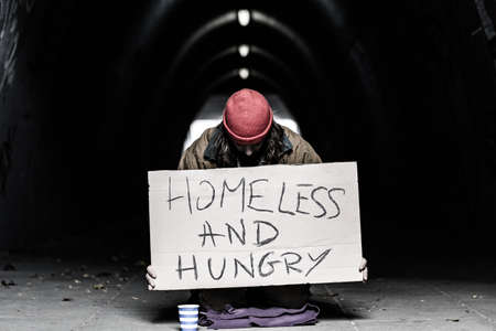 Foto de Homeless and hungry person begging in the shelter of a city against black background - Imagen libre de derechos