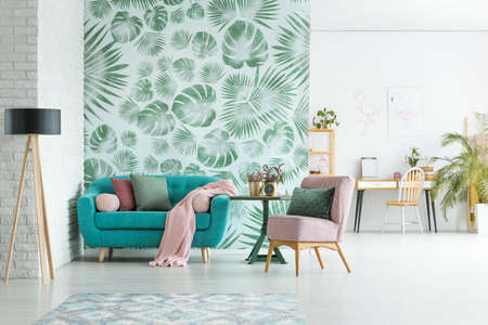 Foto de Turquoise lounge with pink blanket and pillows standing in stylish apartment interior with floral wallpaper - Imagen libre de derechos