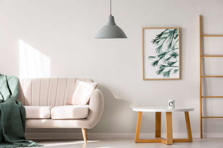 Photo for Blanket on beige sofa near wooden table against white wall with poster in apartment interior with ladder and gray lamp - Royalty Free Image
