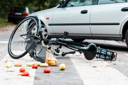 Foto per Crashed bike lying on the street near a car after traffic accident - Immagine Royalty Free