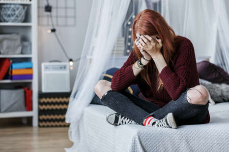 Photo pour Rebellious girl crying on bed because of unhappy teenage love - image libre de droit