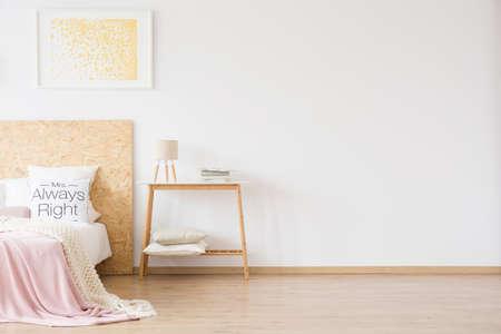 Foto de Feminine bedroom with gold dots painting handing above bed with wooden bedhead and pink blanket - Imagen libre de derechos