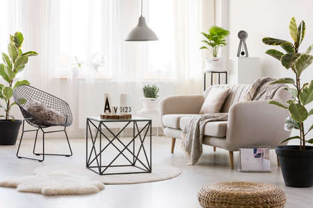Photo pour Black table on white round rug in bright living room interior with armchair and sofa next to plant and pouf - image libre de droit
