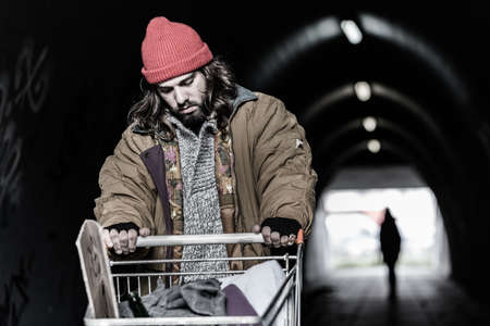 Foto de In the foreground hopeless drifter with trolley looking for shelter in the underpass. Blurred person in the background - Imagen libre de derechos