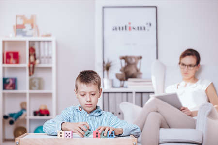 Foto de In the foreground, autistic child playing with colorful cubes and counselor observing his behaviors in the background - Imagen libre de derechos