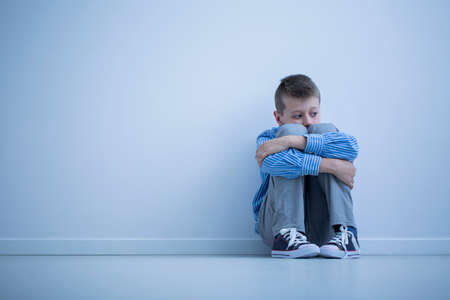 Foto de Young boy with hypersensitivity sitting alone on the floor against the wall with copy space - Imagen libre de derechos