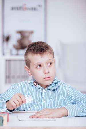 Foto de Close-up of stressed boy doing a puzzle at school. Autistic child during classes concept - Imagen libre de derechos