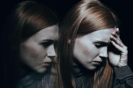 Foto de Face of a pale woman with a migraine and its shadow  - Imagen libre de derechos