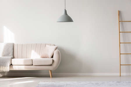 Foto de Beige settee with cushion and blanket against the wall with copy space in flat interior with ladder and lamp - Imagen libre de derechos