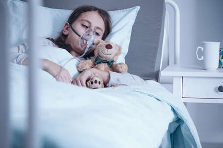 Foto de Kid with cystic fibrosis lying in a hospital bed with oxygen mask and plush toy - Imagen libre de derechos