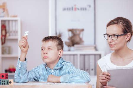 Foto de Rebellious boy doing a jigsaw puzzle during autistic kid therapy with psychotherapist - Imagen libre de derechos