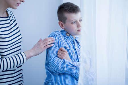 Foto de Worried mother taking care of an autistic child with hypersensitivity - Imagen libre de derechos