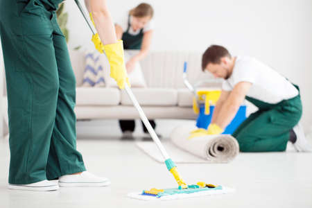 Photo for Cleaner in green overalls cleaning the floor using a mop in bright flat - Royalty Free Image