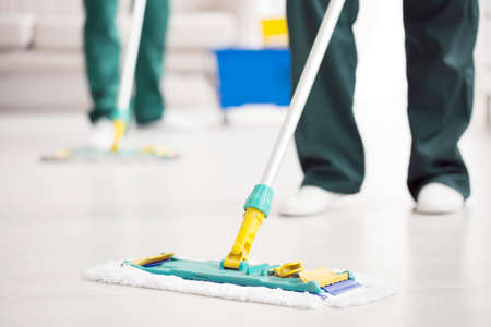 Photo pour Close-up of person holding a floor mop while cleaning a home - image libre de droit