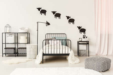 Foto de Patterned pouf near black bed with white bedsheets in teenager's bedroom with sheep stickers on the wall - Imagen libre de derechos
