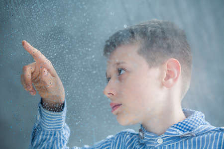 Foto de Photo through the window of autistic child counting raindrops - Imagen libre de derechos