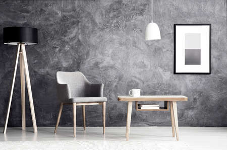 Foto de White lamp above wooden table next to grey armchair in living room interior with poster on concrete wall - Imagen libre de derechos