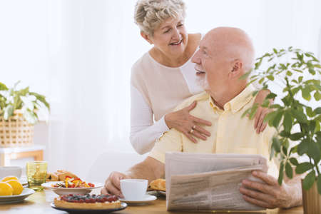 Photo for Elderly woman hugging her smiling husband reading newspaper during breakfast time - Royalty Free Image