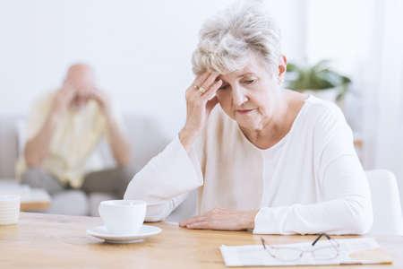 Foto de Sad senior woman sitting at a table after a quarrel with her husband - Imagen libre de derechos