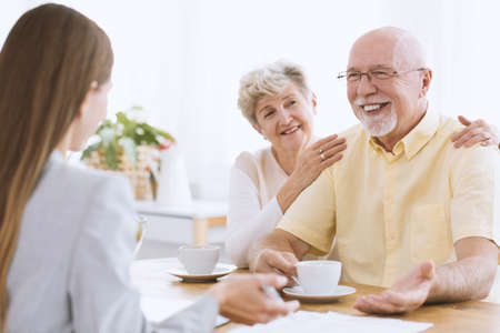 Photo for Daughter visiting elderly parents. Senior woman drinking tea with happy husband - Royalty Free Image