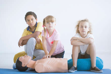 Foto de Multicultural group of children practicing chest compressions on a medical dummy during lesson - Imagen libre de derechos