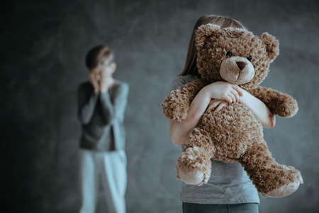 Foto de In the foreground kid holding a teddy bear in the background jealous crying brother - Imagen libre de derechos