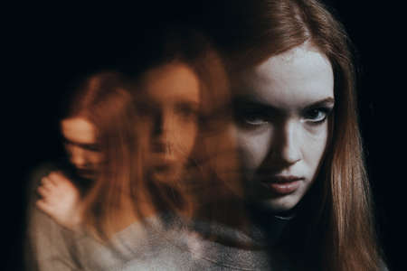 Foto de Blurred figures of a red-haired girl. Concept of mental illness - Imagen libre de derechos
