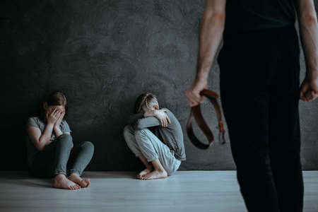 Foto de Angry parent with belt and crying siblings. Children as a victim of domestic violence concept - Imagen libre de derechos
