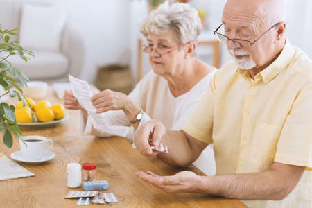 Foto de Senior man taking medication for diabetes while his wife reading a prescription - Imagen libre de derechos