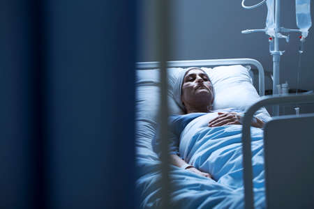 Photo pour Lonely woman suffering from cancer while lying in a hospital bed - image libre de droit
