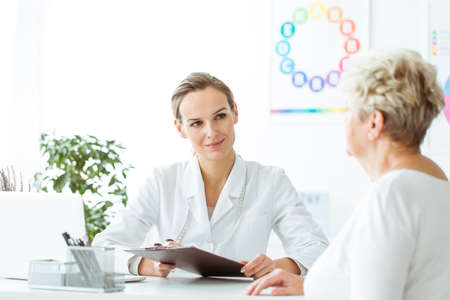 Photo for Smiling dietician taking patient's medical history during a visit at the office - Royalty Free Image
