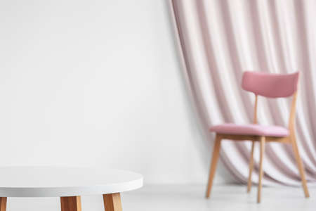Photo pour White wooden round table in the foreground against the wall with copy space and pink chair in the background in bright living room interior - image libre de droit