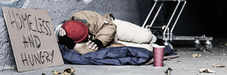 Foto de Panorama of dirty vagrant with sign Homeless and hungry begging in the underpass - Imagen libre de derechos