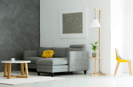 Foto de Plant on wooden stool under lamp next to sofa in grey flat interior with round table and yellow chair - Imagen libre de derechos