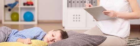Foto de Lonely autistic boy lying on pillows during therapy with psychologist - Imagen libre de derechos