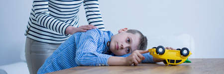 Foto de Panorama of a sick boy playing with a yellow toy and his mother supporting him - Imagen libre de derechos