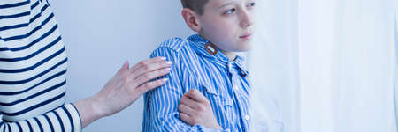 Foto de Close-up of terrified child with hypersensitivity and person taking care of him - Imagen libre de derechos
