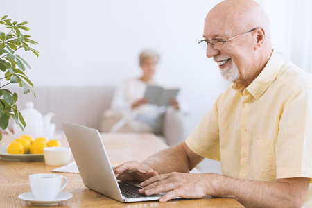 Photo pour Smiling, excited grandfather using laptop and drinking tea - image libre de droit