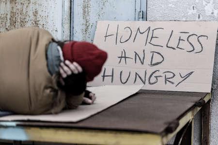 Foto de Homeless and hungry man sleeping next to a handmade sign with text - Imagen libre de derechos