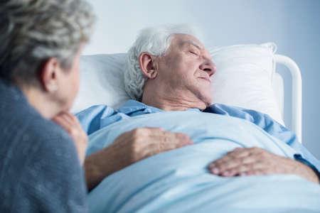 Foto de Dying man lying in hospital bed. Palliative care for an elderly patient - Imagen libre de derechos