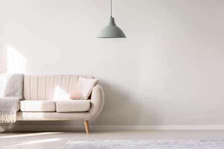 Photo for Beige sofa against white, empty wall with copy space in simple living room interior with lamp - Royalty Free Image