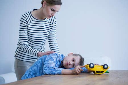 Foto de Concerned mother taking care of her son by touching his back - Imagen libre de derechos