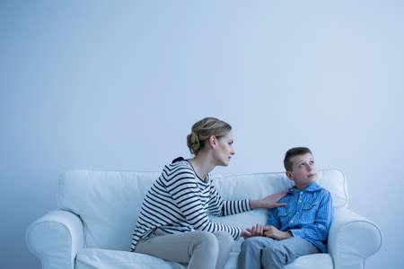 Foto de Protective woman comforting a young, autistic boy in a white room - Imagen libre de derechos